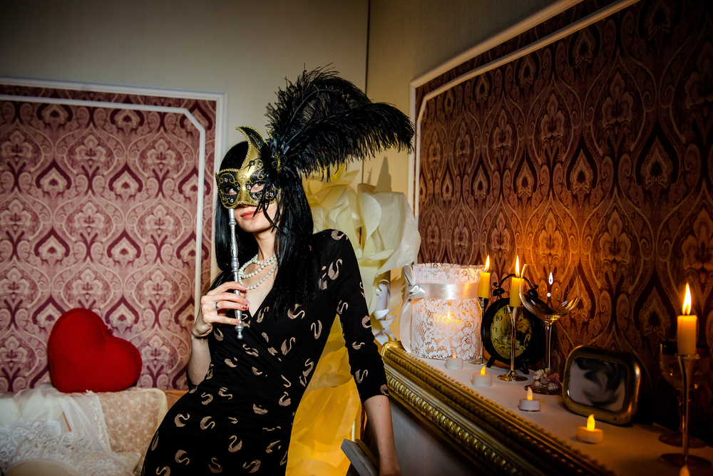 girl in a carnival mask with black feather. Sexy young woman in a smart dress and carnival mask
