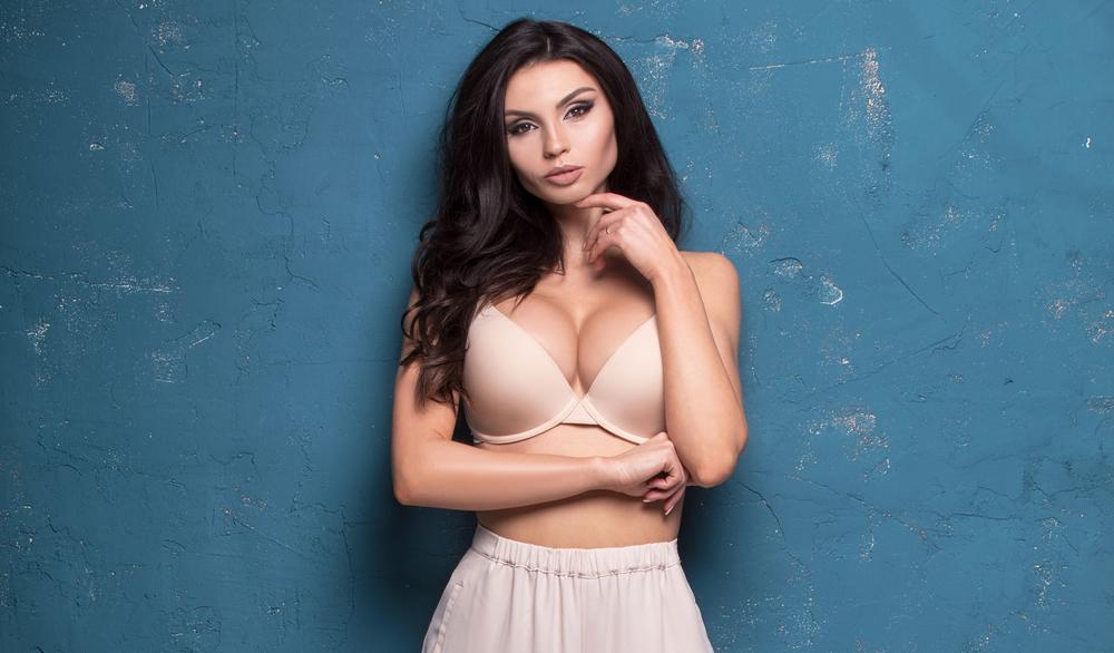 Sensual beautiful woman with long hair and sexy body posing on blue wall, looking at camera.